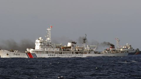 This picture taken from a Vietnam Coast Guard ship on May 14, 2014 shows a Vietnamese Coast Guard ship (R, dark blue) speeding up away from a  China Coast Guard ship  near to the site of a Chinese drilling oil rig (R, background) being installed at the disputed water in the South China Sea off Vietnam's central coast. Vietnam National Assembly's deputies gathered for their summer session are discussing the escalating tension with China over the South China Sea's contested water. AFP PHOTO/HOANG DINH Nam        (Photo credit should read HOANG DINH NAM/AFP/Getty Images)