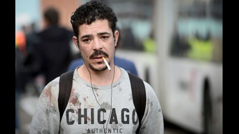 A man with blood stains on his sweater leaves the airport.
