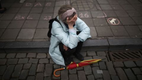 A woman in Brussels pauses after people observed a minute of silence at the Place de la Bourse on March 23.