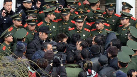 Chinese paramilitary police block access to the residence of a construction firm boss after a group of up to 50 migrant workers stormed past security at the Qijiayuan Diplomatic Compound to protest against what they claim is an unpaid new year bonus in Beijing on January 14, 2013.  Labour unrest and disputes are common before the Chinese New Year when migrant workers are paid for their full years work in a lump sum before heading home to their famillies in outer provinces of the country.    AFP PHOTO/Mark RALSTON        (Photo credit should read MARK RALSTON/AFP/Getty Images)