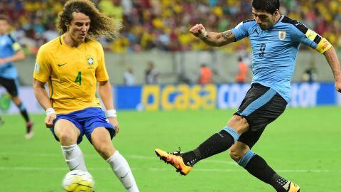 Suarez shoots to score his equalizer as Brazil's David Luiz looks on.