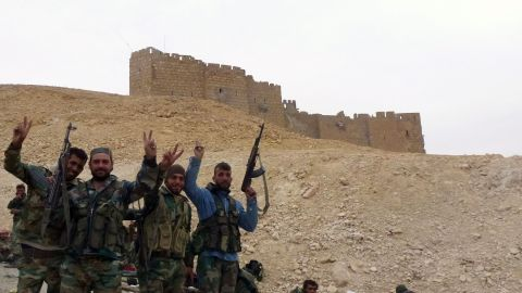Syrian pro-governement forces gesture next to the Palmyra citadel on March 26, 2016, during a military operation to retake the ancient city from the jihadist Islamic State (IS) group. / AFP / Maher AL MOUNES        (Photo credit should read MAHER AL MOUNES/AFP/Getty Images)