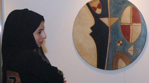 An Emirati woman is seen next to an art work by Farid Belkahia of Morocco prior to Christie's first public Modern and Contemporary art sale in the Middle East in 2006.