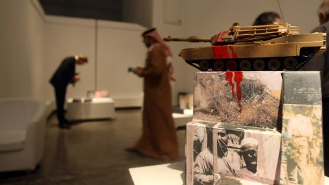 """Visitors look at an artwork entitled """"The Ugly Face of Occupation 2009"""" by Iraqi artist Dia Azzawi displayed at """"My Home Land"""" exhibition in Dubai in 2010. Seven Iraqi artists living outside Iraq took part in the exhibition."""