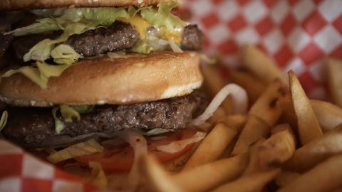 Cheeseburger and French fries, close-up (focus on cheeseburger)