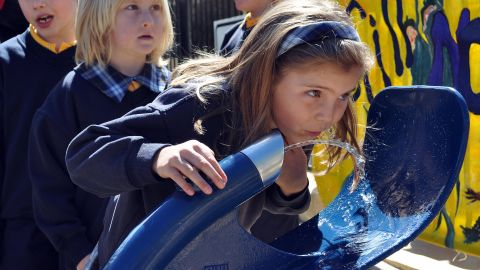Schoolchildren queue to drink from a new public drinking fountain.  AFP PHOTO/Penny SPANKIE
