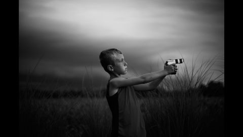 """Tharin plays with a toy gun he made out of cardboard and electrical tape. """"A storm was blowing in and the sky was gorgeous,"""" his mom said."""