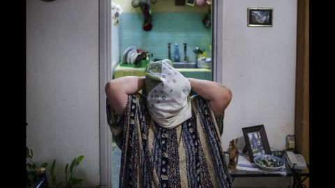 A 72-year-old woman named Shahira struggles with an Islamic scarf. She was an active Christian until three years ago. Now she is member of the Cuban Islamic Committee for Women.