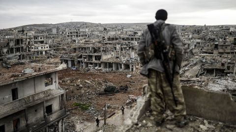 """A Kurdish marksman stands atop a building as he looks at the destroyed Syrian town of Kobani on January 30, 2015. After four months of fighting, Peshmerga forces <a href=""""http://www.cnn.com/2015/02/04/middleeast/kobani-syria-destruction/index.html"""" target=""""_blank"""">liberated the city</a> from the grip of ISIS."""