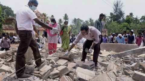 A view of a collapsed building after a massive fire broke out during a fireworks display at the Puttingal temple complex in Paravoor village, north of Thiruvananthapuram, southern Kerala state, India, Sunday, April 10, 2016. Dozens were killed and many more were injured when a spark from an unauthorized fireworks show ignited a separate batch of fireworks that were being stored at the temple complex, officials said. Most of the people died when the building where the fireworks were stored collapsed, said Chief Minister Oommen Chandy, the state's top elected official.(Press Trust of India via AP)INDIA OUT