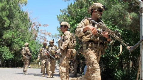 Afghan soldiers walk at the scene of clashes between Afghan security forces and Taliban militants in Helmand province on May 13, 2015. Two heavily armed Taliban gunmen stormed a mosque in the provincial capital Lashkargah, killing at least six people in a seige that lasted several hours and ended with their deaths, officials said. AFP PHOTO / Noor Mohammad        (Photo credit should read NOOR MOHAMMAD/AFP/Getty Images)