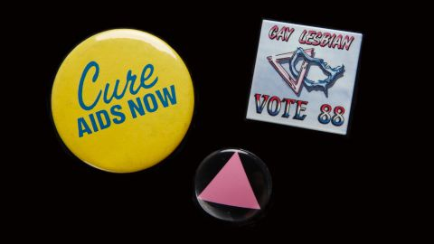 """The AIDS epidemic moved many people out of the closet and into the streets to fight for greater acceptance. Pins were an easy way to signal support. The pink triangle honored LGBT victims of the Holocaust and was a """"reminder of the Holocaust perpetrated by our governments refusing to deal with AIDS,"""" said <a href=""""https://books.google.com/books?id=d5_rAgAAQBAJ&pg=PA585&lpg=PA585&dq=the+time+is+not+right+to+march+on+washington+cathy+woolard&source=bl&ots=9SqK4h_lMo&sig=bEE1unMopqyn6ibfXFN1eyJxKDk&hl=en&sa=X&ved=0ahUKEwiigpGkrvjLAhXLQyYKHZgbAc0Q6AEIHDAA#v=onepage&q=the%20time%20is%20not%20right%20to%20march%20on%20washington%20cathy%20woolard&f=false"""" target=""""_blank"""" target=""""_blank"""">Cathy Woolard in 1989.</a> Woolard, an Atlanta LGBT organizer, went on to be the Atlanta City Council's first female president. The buttons belonged to <a href=""""http://emorymedicinemagazine.emory.edu/issues/2015/fall/features/aging-with-hiv/index.html#RHODES"""" target=""""_blank"""" target=""""_blank"""">Richard Rhodes</a>, a Navy veteran and community organizer who became the first known gay candidate to run for the Georgia House in 1988, and was the first known gay delegate to the Democratic National Convention from Georgia. Every year on his birthday he would get an HIV test. AT 65, he tested HIV-positive. He remains an activist and an advocate for HIV testing."""