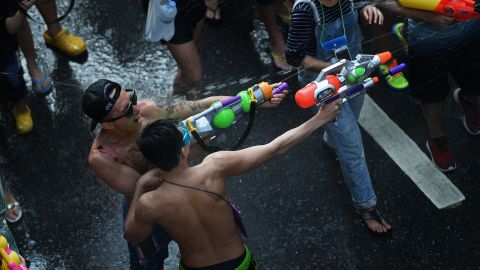 """People take part in water battles as they celebrate Songkran - the Thai new year - in Bangkok on April 13, 2016. Thais and tourists took to the streets on April 13 to drench each other in the mass water fight that marks the country's new year festival Songkran, as authorities attempted to crack down on alcohol, topless dancers and other """"indecencies""""."""