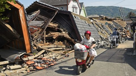 A woman rides a scooter in front of a collapsed house in Mashiki on April 15.