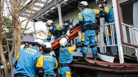 A rescue team removes a man from his damaged house house on April 16 in Kumamoto.