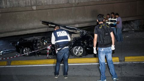 Police check out a car crushed under a collapsed overpass in Guayaquil.