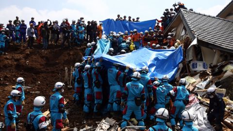 """Rescuers prepare to remove the body of a woman found in a house destroyed by a mudslide in Minamiaso on Tuesday, April 19, in the aftermath of a 7.0-magnitude quake on Kyushu Island. The same region was hit by a <a href=""""http://www.cnn.com/2016/04/14/asia/japan-earthquake/"""" target=""""_blank"""">6.2-magnitude quake</a> on Thursday, April 14."""