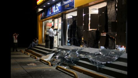 A security guard protects a store damaged by shock waves from the explosion.
