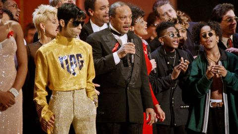 """As dozens of singers perform """"We Are The World"""" on the 10th anniversary of the African famine relief anthem, the artist formerly known as Prince stands sucking on a lollipop next to Quincy Jones at the American Music Awards in Los Angeles in 1995."""