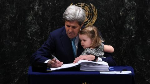 Secretary of State John Kerry signs the Paris Agreement with granddaughter Isabelle Dobbs-Higginson.