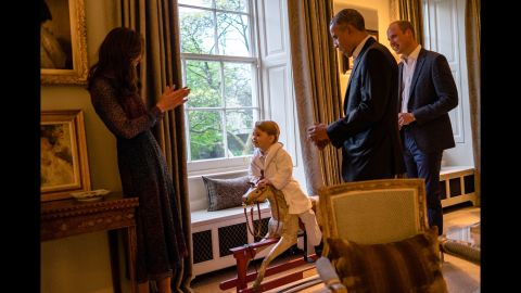 """US President Barack Obama talks with Prince William as Catherine plays with Prince George in April 2016. The President and his wife <a href=""""http://www.cnn.com/2016/04/18/politics/gallery/obamas-meet-royals/index.html"""" target=""""_blank"""">were visiting Kensington Palace.</a>"""