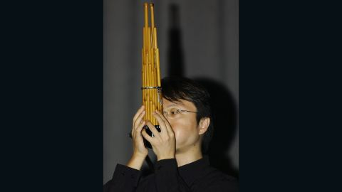 """A Japanese musician plays a traditional Japanese musical instrument called """"Sho"""", which is made up of 17 slender bamboo pipes with reeds gathered together in one bundle. It makes a sound similar to an organ."""