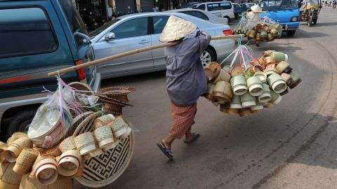 A woman in Laos carrying handmade bamboo baskets, a typical sight across many parts of Asia.