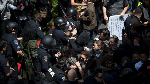 Police and protesters clash outside the Hyatt Regency Hotel where US Republican presidential candidate Donald Trump was speaking in Burlingame, California on April 29, 2016.   Hundreds of protesters jostled with police in riot gear outside a California hotel where Republican presidential frontrunner Donald Trump was to give a speech, forcing the candidate to duck into a back entrance. / AFP / Josh Edelson        (Photo credit should read JOSH EDELSON/AFP/Getty Images)