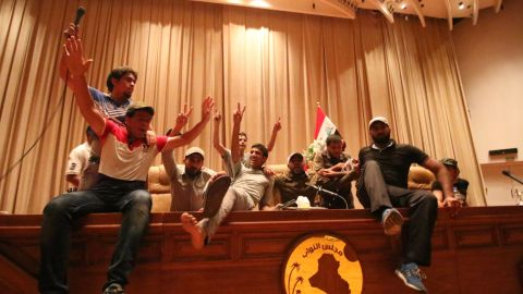 Iraqi protesters flash the V-sign as they gather inside the parliament after breaking into Baghdad's heavily fortified green zone on Saturday, April 30.