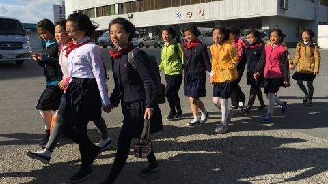 """Secondary school students walk home in a group along Kwangbok """"Liberation"""" street in Pyongyang on May 4 after a day of work and rehearsals for the upcoming congress."""