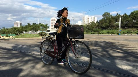 """A woman walks her bike along Kwangbok """"Liberation"""" street in Pyongyang on May 4 after a day of work and rehearsals for the upcoming congress."""