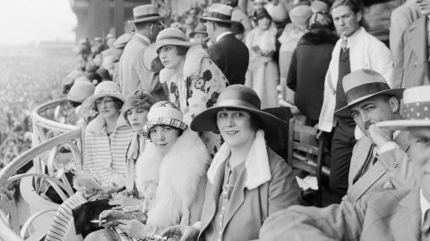 """The Derby first launched in 1875, and up until the turn of the 20th century women could be seen wearing hats, gloves, and long dresses down to their ankles.<br />""""At any social outing in America at that time, you would have worn a hat and gloves -- and the Kentucky Derby was no different,"""" said Chris Goodlet, Curator of Collections at the <a href=""""http://www.derbymuseum.org/"""" target=""""_blank"""" target=""""_blank"""">Kentucky Derby Museum.</a><br />""""Many women would have worn silk because of the warm weather, and be carrying a parasol.""""<br />This image features race-goers in 1926."""