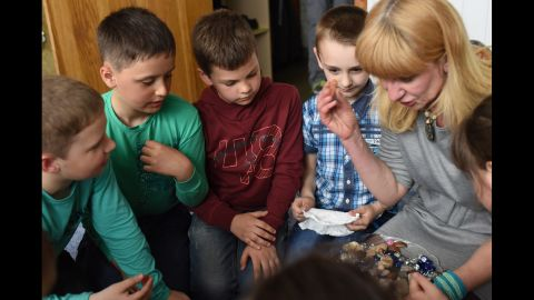 """A psychologist leads children taking part in a group """"sand therapy"""" session at Promir Centre for Psychotherapeutic support in Slovyansk, eastern Ukraine."""