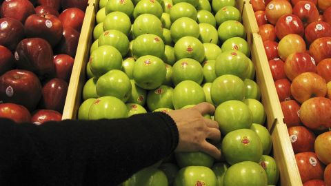"""BEIJING - JANUARY 27:  A shopper chooses granny smith apples at the newly-opened Tesco supermarket on January 27, 2007 in Beijing, China. The UK giant opened its first own-brand supermarket in Beijing after investing in 46 stores across China under the name of its Chinese partner, Le Gou, which translates as """"Happy Shopping"""". Tesco's new store in Beijing is competing with other international chains that are well established in China, such as Wal-Mart and Carrefour.  (Photo by Andrew Wong/Getty Images)"""