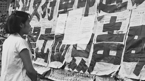 """A girl reads big character posters (dazebao) covering the windows of a department store in Guangzhou. Such posters were used for spreading propaganda and attacking """"class enemies."""""""