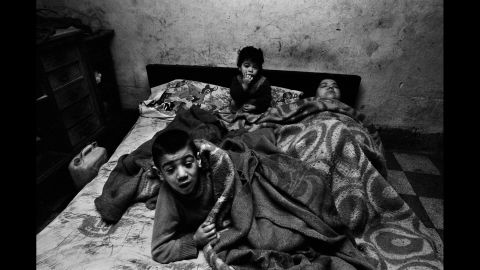 """A woman and her children are photographed in Palermo in 1978. """"I was shooting poor people, and I entered a house around noon,"""" Battaglia said. """"I asked her, 'Why are you in bed at this hour?' and she said, 'I have no fire, no light, no food ... what can I do?' People brought her spaghetti, but she was always in bed with the children. I always wondered what happened to this woman and those children."""""""
