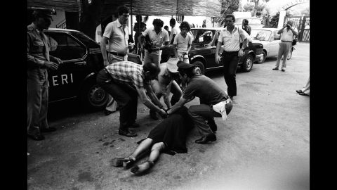 A woman falls to the ground after hit men killed a hotel owner in Capaci, Italy, in 1980.