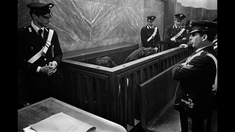 Men accused of organized crime hide from cameras at a trial in Milan, Italy, in 1971.