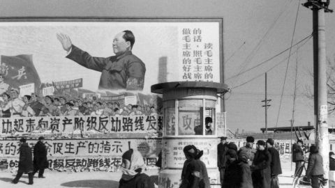 """Beijing residents walk past a huge poster of Mao during the Cultural Revolution. The poster calls on people """"to be good soldiers of Mao Zedong."""""""