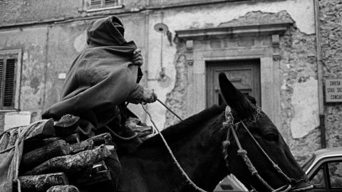 A man covers himself with a cloak in the streets of Sicily in 1989.