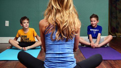 Dana Santas teaches her son Luke, left, and his best friend, Nolan Joyner, the cobbler's pose.