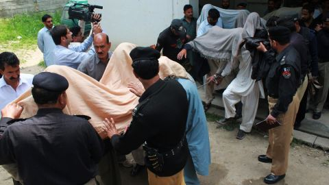 """Pakistani police escort suspects accused of killing and setting fire to a woman as they arrive at a court in Abbottabad on May 5, 2016.   A Pakistani woman was drugged, strangled and then her body set ablaze because she helped her friend elope, police said May 5, announcing the arrest of 14 people in a twist on the grim practice of """"honour killings"""". / AFP PHOTO / SHAKEEL AHMEDSHAKEEL AHMED/AFP/Getty Images"""