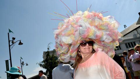 A festive fan poses in a hat resembling an explosion of pastel ruffles.
