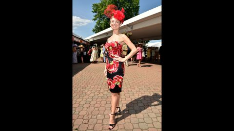 A fan wears a floral themed dress and matching hat.