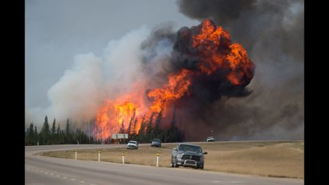 A ball of flame rises behind abandoned vehicles on Highway 63 near Fort McMurray on Saturday, May 7.