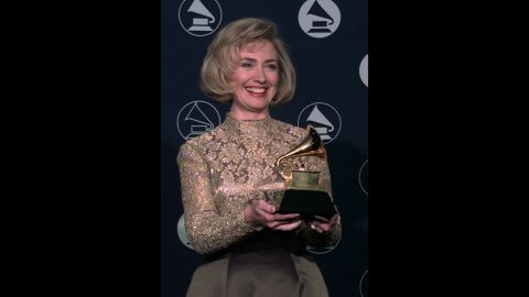 """The first lady holds up a Grammy Award, which she won for her audiobook """"It Takes a Village"""" in 1997."""