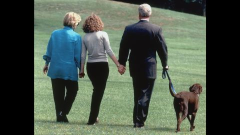 The first family walks with their dog, Buddy, as they leave the White House for a vacation in August 1998.