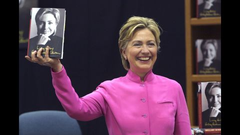 """Clinton holds up her book """"Living History"""" before a signing in Auburn Hills, Michigan, in 2003."""