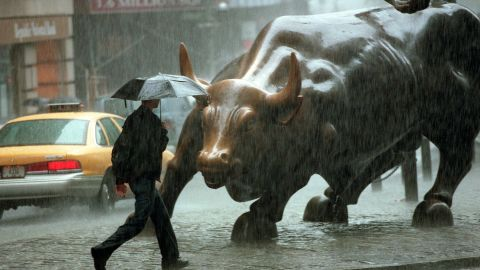 NEW YORK, UNITED STATES:  A pedestrian passes in front of a statue of a bull in the Wall Street area in New York City where rains from Hurricane Floyd hit 16 September, 1999.  Floyd made landfall in Wilmington, NC and Federal Emergency Management Agency chief James Lee Witt said 16 September 1999 that this is a major disaster for North Carolina. (Photo credit should read DOUG KANTER/AFP/Getty Images)