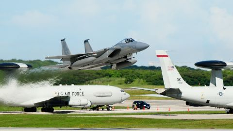 An F-15 Eagle takes off from the Andersen Air Force Base, Guam, flight line as two E-3 Sentries are seen in the background.